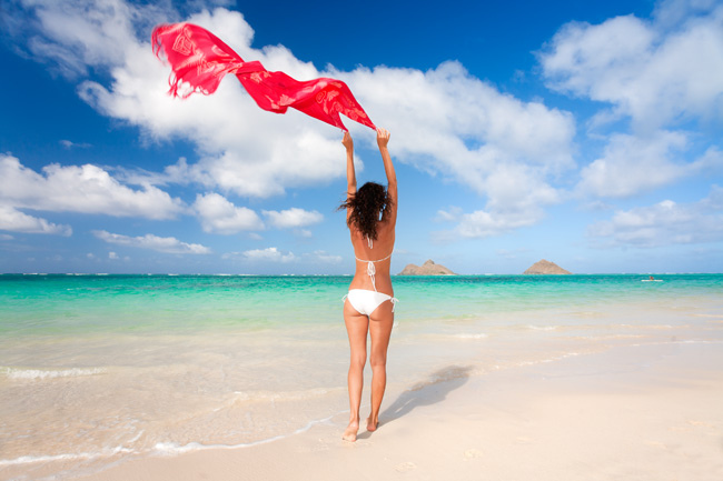beautiful attractive woman in bikini on lanikai beach in hawaii with sarong and mokulua islands
