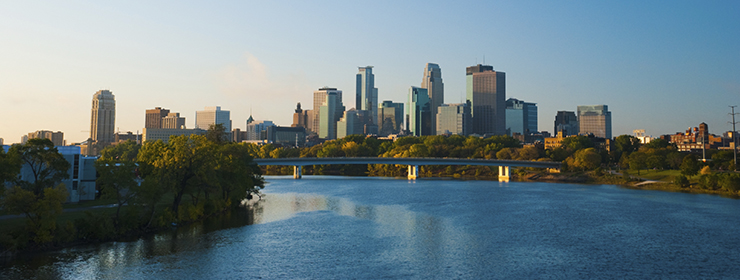 Downtown Minneapolis skyline in the Morning with a bridge midway and the Mississippi River in the foreground.